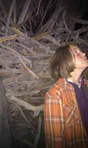 Maret gazing at a huge hut formed out of drift wood woven together for walls