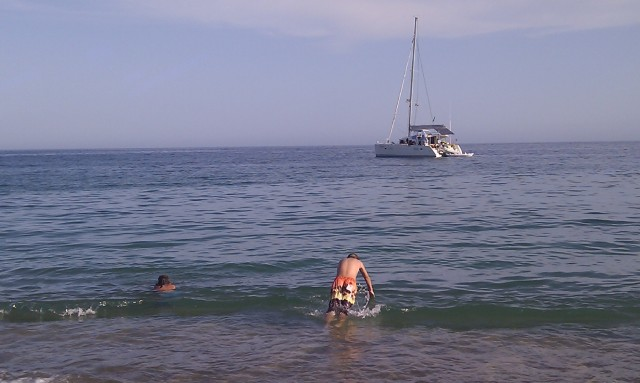 Alex (the one diving in) and his family now live on the catamaran you see.  They are from California sailing to Australia.
