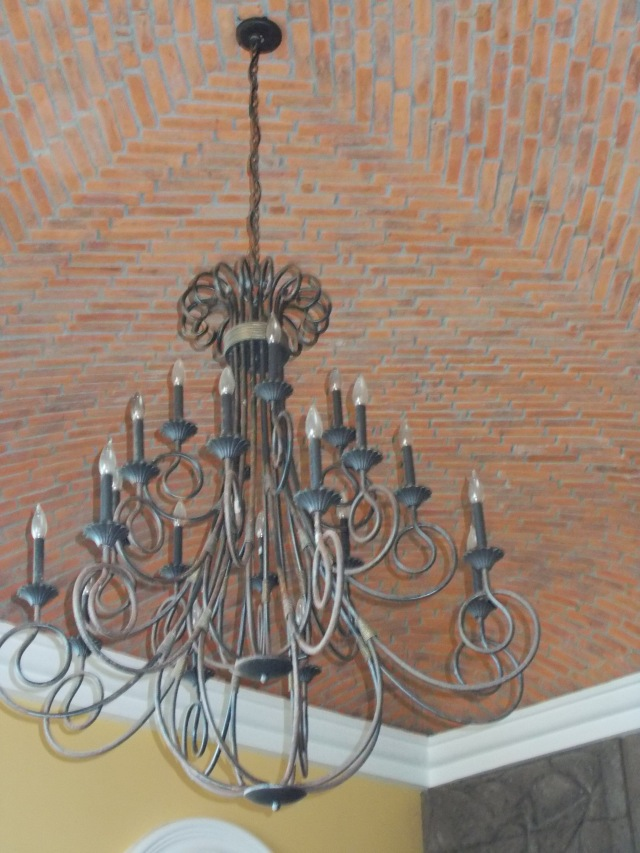 Dining room chandelier with cool brick ceiling