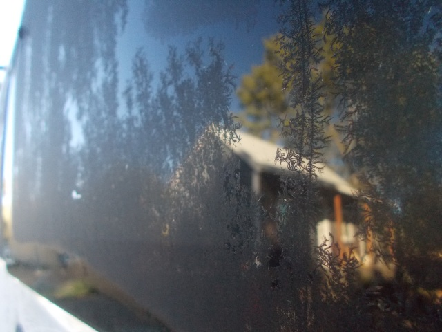 Cool reflection of the cabin in the van's back window with a small forest of jackfrost.