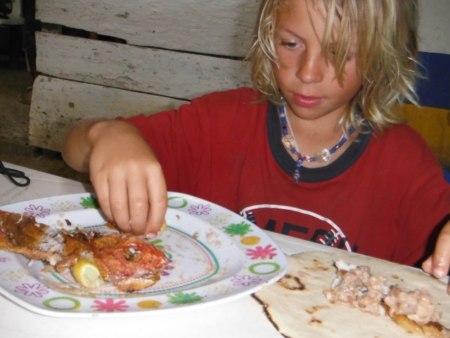 Anders' meal, putting pieces of fish into his tortilla along with fried beans and salsa.  Roll up yumminess.