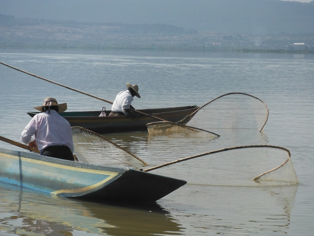 Upon approach to the island about 6 men demonstrate traditional fishing practices