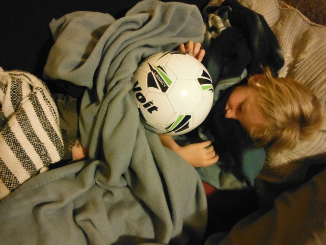 Laars exhausted after a big swim, he puts himself to bed, cuddling  with our soccer ball.