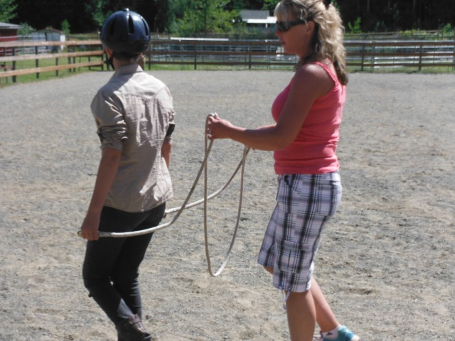 Shelly gives signals to the 'horse' Maret for her to get the idea of how the horse will receive messages down the ropes.