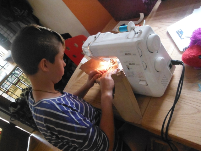 Maret and Mitchell are designing and sewing a leather dress for Marin.
