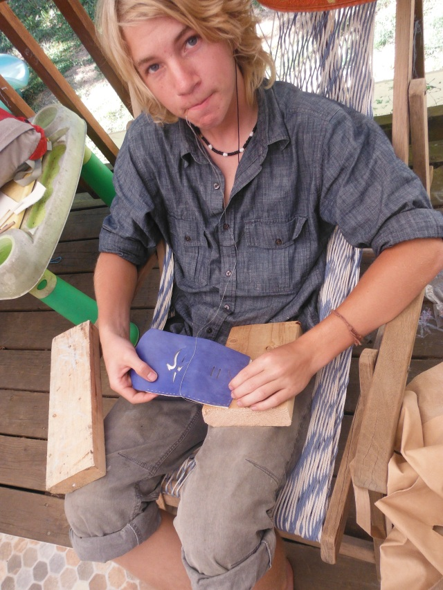 Mitchell working blue leather into a small journal cover.